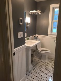 Tiny bathroom remodel. Paint is Rock Gray by Benjamin Moore. Tile is Hampton Hermosa set on the diagonal. Sconces, medicine cabinet, sink fixtures, and train rack all Pottery Barn. Sink and toilet are Kohler. #smallbathroomrenovations