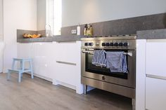 Prachtige #leefkeuken. Stijl: witte hoogglans keuken als basis in combinatie met extra dik #Paëllastone werkblad voor een stoere uitstraling en een fornuis van La Germania. www.keukenhofvanholten.nl
