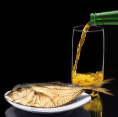 Пиво и рыба на черном фоне фото со стока