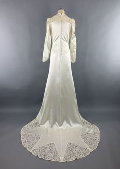 This is a stunning vintage wedding dress made in 1940. Ivory bias cut rayon duchesse satin with lace shoulders and collar. Long sleeves with pointed cuffs, covered buttons up the back, and beaded trim