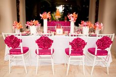 Pretty pink rosettes and chair pads punch up plain white chairs.Photo…