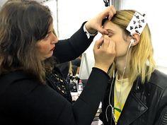 Cartas de baralho são usadas para não marcar o cabelo das modelos na hora de prendê-los para maquiar. | 21 imagens que mostram a real dos backstages da Semana de Moda de Paris
