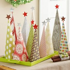Imagine a little forest of these fun paper trees among your Christmas mantel decor or as a dining table centerpiece! http://www.bhg.com/christmas/holiday-ideas/?socsrc=bhgpin110614decorativepapertrees&page=4