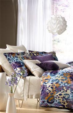 Modern bedroom design featuring gorgeous colors and unique prints. love that light fixture!