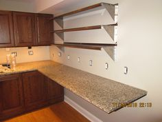 "Kitchenette with 25"" by 76"" wall hung granite countertop. Heavy steel 27"" in-wall free hanging shelf brackets from The Original Granite Brackets company. Used cabinets and granite from Craigslist."