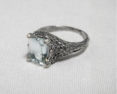 A tremendous amount of exquisite filigree surrounds this beautiful, genuine 4 carat blue aquamarine gemstone ring. The stone is eye clean. It