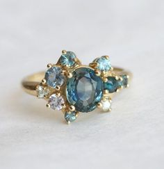 Beautiful teal bi color sapphire cluster ring. All other stones are also sapphires and blue diamonds. Ring features 1.1 ct bi color teal blue green sapphire sapphires blue diamonds Sizes available: 3.5-8 (Larger and smaller sizes are available. Priced upon request) Please note needed size when checking out.Metal Available: 14k rose/white/yellow gold ITEM WILL BE SHIPPED WITH EXPRESS SHIPPING - DHL EXPRESS SHIPPING Please select your size at the drop down menu. Thanks! ♥, Maya ★ ...