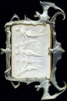 Lalique 1902-03 'Dancing Nymphs in a Frame of Bats' Brooch: centering on a carved French artificial ivory plaque, depicting five dancing nymphs in relief, w/in a blue enamel bat frame, mounted in 18k gold. christies.com