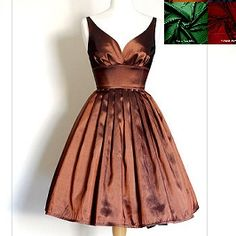 This stunning evening dress is made from a beautiful copper taffeta fabric. The plunging neckline at the back and bust gathering make for a classic 1950's evening look and the full skirt can be emphasized with a petticoat (as pictured - petticoat not included) for extra glamour or left to fall naturally. Perfect for proms, winter balls and Christmas parties! By Dig for Victory