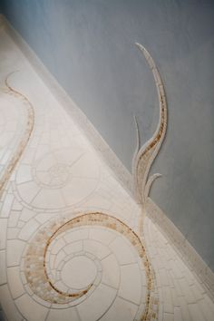 exquisite hand-cut marble and limestone mosaic that unfurls up the subtly reflective, pale-blue Venetian plaster walls.