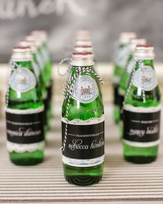 Small bottles of Pellegrino adorned with a piece of baker's twine served as place cards. Custom name labels were fixed to each bottle with a piece of scalloped lace underneath.