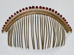 An antique French Empire gilt diadème or tiara, with a row of 29 faceted faux garnet gems along top. The elaborate cast gilt metal has a design of grapes on a vine, and floral pierced work. The faceted glass jewels are excellent faux gems, much resembling real garnets with variations in coloration, seen when held to the light, and imperfect cuts. This tiara is more restained in design than are many others.  CONDITION: No cracked or missing stones. One tine missing at one end, two tines…