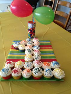 "Rainbow/primary color cupcakes made into a number 1 cake.  ""Tray"" is cardboard covered in colorful wrapping paper. Centerpiece is glass vase filled with gum balls and 2 balloons.  Balloons are secured on a simple grilling skewer that was painted.  Add a ribbon to the top of the vase to complete the look"