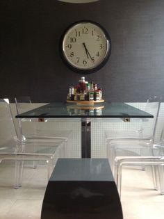 Detalle del office de la cocina. Mesa de CATTELAN en acero y cristal. Sillas en metacrilato trasparente y papel en tela de saco de ELITIS. Parte baja azulejada con HISBALIT en blanco.