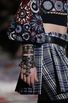 Alexander McQueen Celtic check kilt worn with a crocheted Fairisle jumper and hand jewellery.