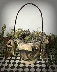 This little Easter basket is made from a peat pot. It stands 8.5 inches tall including the handle. The pot itself is almost 4 inches tall with a diameter of 3.5 inches. The peat pot has been painted white and antiqued with brown ink. A Victorian graphic of a rabbit has been