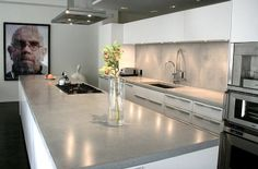 A concrete counter with a polished finish in a kitchen by architect Francis D'Haene of D'Apostrophe Design. Placing hot pans directly on concrete counters won't harm the concrete, but may discolor the sealant. cutting boards and trivets are recommended.