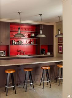 A pop of red brightens a bar area | archdigest.com