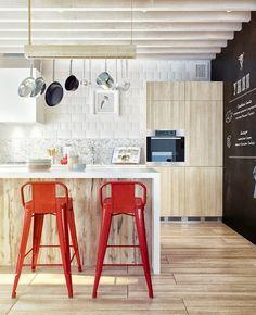 Plein de choses intéressantes dans cette cuisine : la suspension à ustensiles drôlement plus contemporaine que ce qu'on a l'habitude de voir, le mur tableau noir et les tabourets de bar rouges qui font écho à la cocotte Le Creuset et le blender KitchenAid !