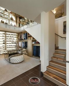 A tight squared staircase connects the two levels of this contemporary closet. On the lower level, a rolling ladder allows easy access to the top shelves. The top level has tons of built-in cubbies for purses and shoes that are backlit.