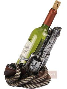 Porta vinho Country Importado Duas Pistolas Enroladas com Corda Velha    Porta garrafa de vinho. Produto importado. Design de duas pistolas antigas de cano cor prata envelhecida com sombreados pretos e desenhos. Pistolas viradas para cima apoiadas em uma base arredondada feita de corda velha com detalhes de couro enroladas. Fabricada em resina endurecida pintada mão. Incrível riqueza de detalhes, perfeito acabamento que faz com que a peça pareça real.