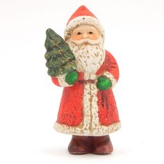 SOLD - Pre-owned collectible porcelain ceramic Santa Claus figurine. The bisque porcelain ceramic Santa Claus is carrying a Christmas tree in one arm and dressed in a long red coat, red hat and brown boots.
