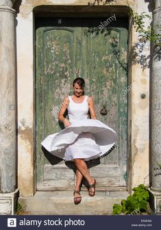 Download this stock image: Italy, Ravello, Woman standing in front of watered wooden door, wind blowing woman's dress - EN3H5A from Alamy's library of millions of high resolution stock photos, illustrations and vectors.