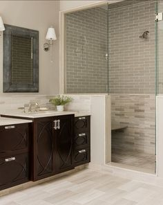 Dark cabinets, rectangular floor tile, grey subway tile mixed with carrara marble in the shower enclosure