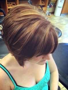 Short inverted bob haircut. Chocolate brown hair color with medium blonde highlights.