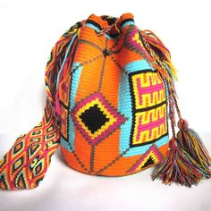 $90.00 TAYRONA MOCHILA. About Wayuu Mochilas: These crochet Wayuu bags are made by Wayuu women and designed by Lombia & Co. The colors of the mochilas Wayuu are inspired by the vivid colors that surround region of La Guajira. Sand, sea, desert, sun and a clear sky are constants in the landscape. Geometric figures are a signature of these mochila bags.