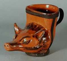 An English Redware Pottery Stirrup Cup,    Circa 1775.      An unusual redware pottery stirrup cup.  The shape is most unusual being an upright L-shape form now mounted with an old metal holder and handle.    The cup is in the form of a vixen's head with features of the fur highlighted in a black wash.  The opening of the cup is at 90 degrees to the fox's head so that the cup could actually rest on a small concave base.      Height: 4 inches; width: 6 1/4 inches
