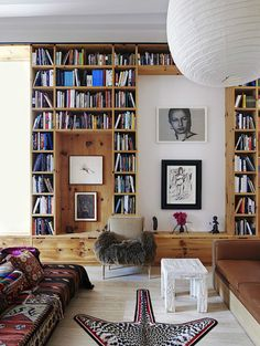 Living Room - Pine shelving houses a book collection & frames works from photographers Inez and Vinoodh's art collection in their New York loft. The faux-bois plaster table is by John Dickinson. A wall of vast interests. New York Loft, Loft Spaces, Living Spaces, Living Rooms, Living Area, Small Spaces, Floor Seating, Home Libraries, Architectural Digest