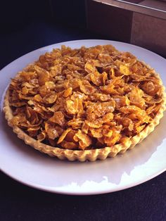 Cornflake tart another school classic Sweet pastry case 4oz butter 1/2 cup of golden syrup 1-1/2 to 2 cups of cornflakes Melt the butter add the syrup till all melted then cover the cornflakes Spread some jam of your choice on the pastry case then scoop scoop scoop lol until pie all filled Then wahlaa cornflake tart ....to be tried with chocolate custard