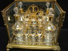 """French TANTALUS Set with Gilt Leaf Design: Consisting of Four Crystal Decanter, 13 Crystal Cordials Housed in Brass or Bronze Frame. Each Glass with Gilt Leaf Design. Decanters have Original Hollow Blown Stoppers. Etched Panels with Matching Leaf Design. Frame & Crystal Further Housed in Brass or Bronze Box, Glass Top & Sides on Acanthus Leaf Feet. Decanter 8""""T; Case 11 1/2""""T X 13""""W X 10 5/8""""D."""