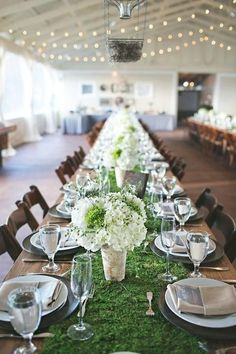 Nothing says 'woodsy' like moss. This turf-like wedding table runner below is a great example of how to incorporate Mother Nature's elements into your wedding tablescapes. A moss table runner for a rustic wedding table with birch vases and white flower centerpieces will leave your guests speechless. Check out more wedding table runner ideas here: http://www.mywedding.com/wedding-ideas/colors-themes/9-trending-table-runners-for-weddings/ #howtodecorateweddingcandles