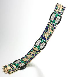 ENAMEL, LAPIS LAZULI AND DIAMOND BRACELET, 1920S.  The reversible band depicting ancient Greek scenes of ladies worshipping Athene on one and a battle scene on the other side, highlighted at intervals with rotatable plaques millegrain set with circular-cut diamonds set at the centre with polished lapis lazuli, length approximately 175mm.