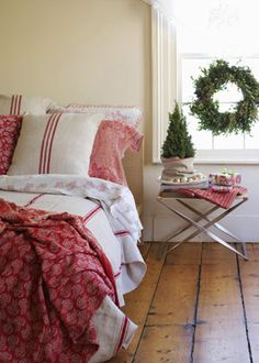 holiday guest room    In the bedroom, favorite vintage linens that have been washed a thousand times add softness and a touch of traditional color to the bed. On the bedside table, a fragrant pot of rosemary mimics a mini evergreen. (An old pillowcase hides the container.)