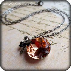 Georgia Peach: lush peach vintage glass jewel and gunmetal bow charm necklace