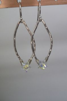 Sweet star drop earrings catch the winter light.  A sparkling Swarovski crystal star is wire wrapped onto a handmade fine silver marquise shape.