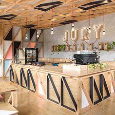 Jury Coffee| Melbourne Project: Biasol Design Studio  A cafeteria se encontra em Pentridge, um vilarejo de Melbourne, onde antes funcionava uma prisão. No projeto foram utilizados materiais em sua forma natural, como concreto e madeira compensada, cores e objetos de design, criando uma atmosfera mais leve, em contraponto ao passado do local.