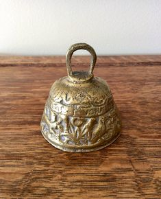 "Gorgeous solid heavy brass church/sanctuary bell. Evangelist bell with embossed animals & Latin saying. Working bell in good vintage condition! Great office decor, bookshelf decor, dresser top, or shadow box decor. Shipped insured! Measures total 2.5"" height x 2 & 3/8"" diameter"