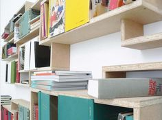 'A quite arbitrary number of shelf boxes in different heights, cutting and turning round each, are forming this shelf. Every crate is oriented in its height and depth on a pair of books and forms an individual frame for it. Put into grooves, with an extended lid each, the books are forming small hinged storage spaces in the shelf,'