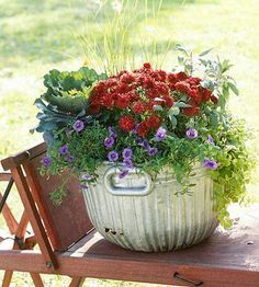 Tuck a variety of annuals, perennials and grasses into an antique galvanized container for a pretty fall container garden. More fall container ideas: http://www.midwestliving.com/garden/container/16-fall-container-garden-ideas/