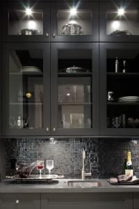 Glossy black butler's pantry with glass-front kitchen cabinets, gray quartz countertops and glossy black glass tiles back splash.  the light reflected on the tiles make the treatment effectiove