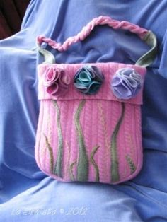 This bag is a total upscycle other than the hand dyed wools used to  make the flowers and stem appliques. The pink body is a felted wool sweater, orginally from the GAP, but picked up at the local thrift shop. The lining is silk from a ten year old skirt whose fabric I always admired and couldnt throw out.  The pattern is my own design. I used Decor Bond and a bit of Peltex in the bag body and weft insertion interfacing on the silk lining. The handle is made up of a braid using the front f