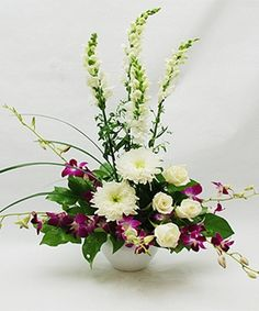Beautiful design of White Snapdragons, White Fuji Chrysanthemums, Lavender Dendrobium Orchids accented with White Roses. Available for Same Day Local Delivery Available for Same Day Nationwide Delivery Purchase at any Norfolk Florist. Beach Flowers, Summer Flowers, Summer Flower Arrangements, Floral Arrangements, Get Well Flowers, Memorial Flowers, Dendrobium Orchids, Same Day Flower Delivery, Mothers Day Flowers