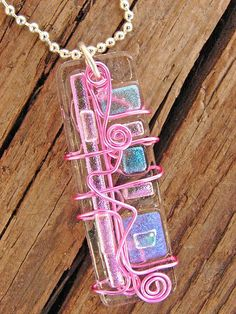 A pinkish wire was wrapped around a dichroic GLASS pendant. It totally looks like I should try to finish one!!!