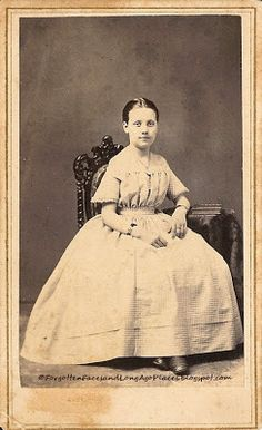 "second girl who appears to be a bit older, perhaps ten or eleven,  is also wearing the off-the-shoulder style in a belted, gingham dress.  She also is wearing a necklace, bracelet and ring.  This photograph was taken between 1864 and 1866 as evidenced by the revenue stamp and initialed by the artist ""RB."""