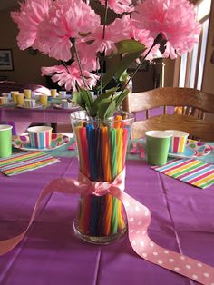 """Edible"" centerpieces includes a narrow bud vase with silk flowers inside a larger vase into which rainbow Twizzlers were placed.  The licorice echoes the stripes on the napkins and fruit cups.  A ribbon finishes off the centerpiece."