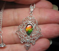 "Delicate and Unique pear-Shaped Ammolite Pendant - Sterling silver filigree setting - 1.57"" (40 mm) top of bail to bottom of pendant - 0.35"" (9 mm) length - 0.23"" (6 mm) width"